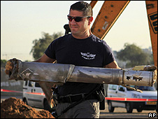 Israeli police officer carries away the Grad rocket