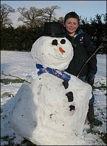 Max Harris building a snowman in Hurn, Dorset - pic Kevin and Sarah Harris