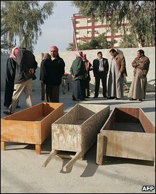 Iraqi civilians stand near open coffins
