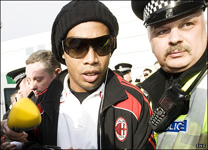 Ronaldinho gets a police escort through the media scrum