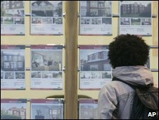 Man looks in estate agent's window