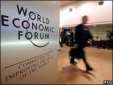 A participant walking past a sign at the World Economic Forum (Photo: FABRICE COFFRINI/AFP/Getty Images)