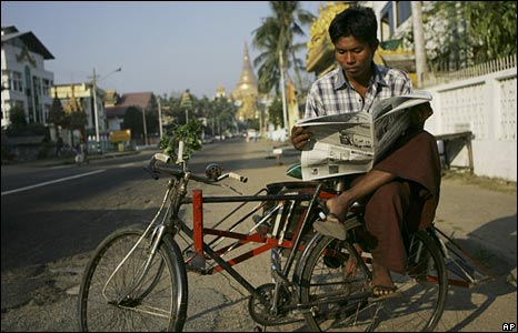 A bicycle taxi driver reads a newspaper in Burma's commercial capital, Rangoon