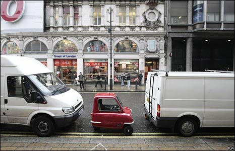 The world's smallest legal car sits parked between two vans in London