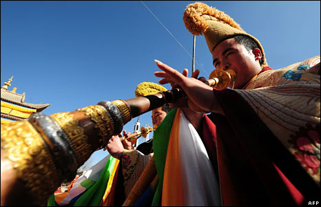 A Tibetan Buddhist monk blows his horn at a monastery in Repkong, Qinghai province, China