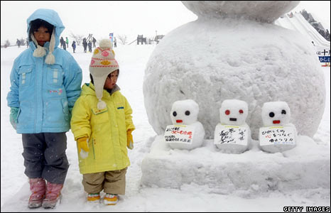 Two children stand next to a snowman in Sapporo, Japan