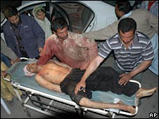 A wounded man is carried on a stretcher after an explosion in Dera Ghazi Khan