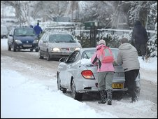 People pushing their car in the snow
