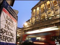 Traffic passes a newspaper poster featuring the Bank of England's latest interest rate cut, outside the Bank of England