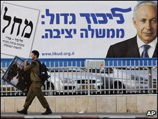 A man walks past an election poster for Benjamin Netanyahu