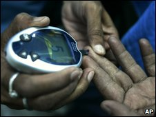 Nurse checks blood sugar of a diabetic