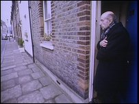 An older man standing outside the front door of his house