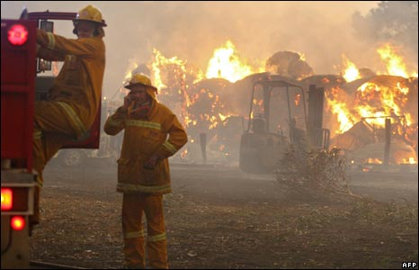 Country Fire Authority (CFA) volunteers prepare to move to save another house as a barn burns in the background close to Labertouche, some 125 kilometres west of Melbourne, on February 7, 2009