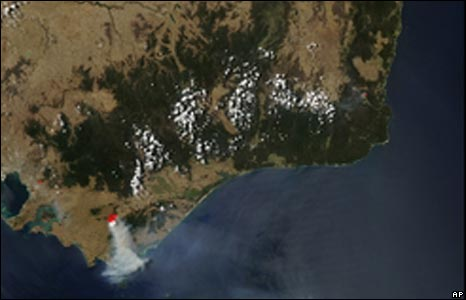 This image provided by NASA shows a large plume of smoke spreading southward from a fire (outlined in red) that appears to be burning in a small area of forest west of Churchill in Victoria's Gippslan