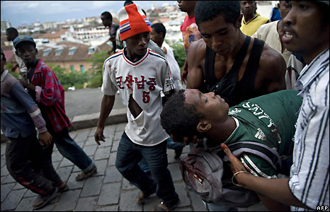 A wounded man is carried in Antananarivo
