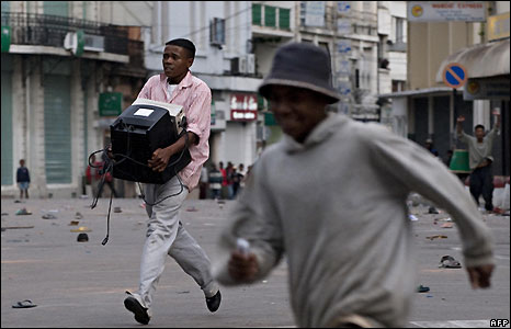 A man carrying a computer monitor runs in Antananarivo