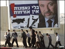 Ultra-Orthodox children walk past a poster for Avigdor Lieberman