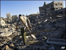 Hamas member walks through ruins in Gaza City
