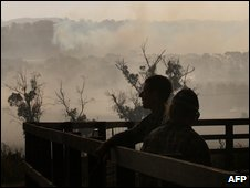 Residents survey the burning countryside around Labertouche, Victoria