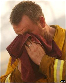 Australian firefighter wiping face with towel