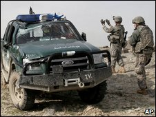 US troops inspect an ambushed vehicle near Kabul. Photo: February 2009