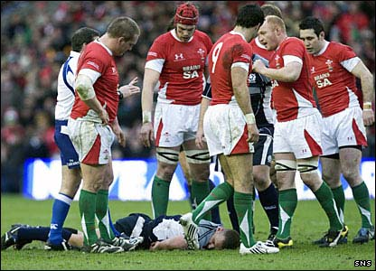 Concerned Welsh players surround the injured Geoff Cross of Scotland