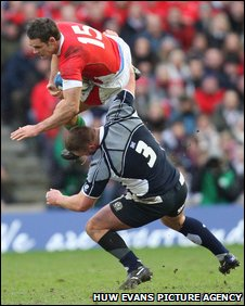 Lee Byrne is challenged in mid-air by Geoff Cross, whose game was ended