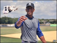 Alex Rodriguez throws a batting glove to fans in Boca Chica, Dominican Republic