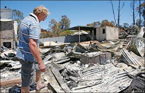 A man surveys the damage in his backyard after a bushfire in Bendigo, Victoria