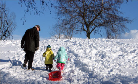 Adult and children with sledge