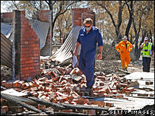 Investigators survey the ruins of a house