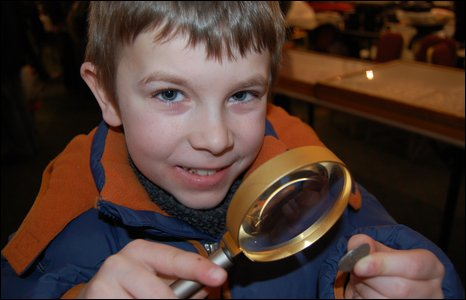 Dylan Adams studies a coin at the Midland Coin Fair