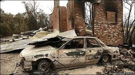 A burned out car and house following bushfires in Christmas Hills, Australia
