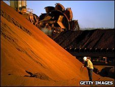worker inspects iron ore