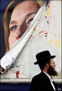 Un judío ultraortodoxo pasa al lado de un póster destruido de la líder del partido Kadima, Tzipi Livni, en Jerusalén.