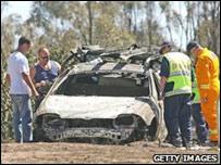 Policías examinan auto incendiado