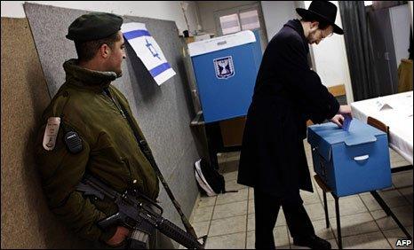 An Israeli border policeman and a Jewish Orthodox man at a school in Jerusalem