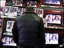 Man watching flat-screen televisions in a shop