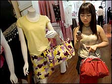 A Chinese woman shops at a clothes store in Beijing (BBC)