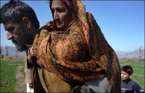 A man carries his elderly mother on his back as they flee from Swat