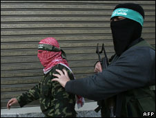 Two members of Hamas's military wing leave a press conference in Gaza City on 19 January 2009