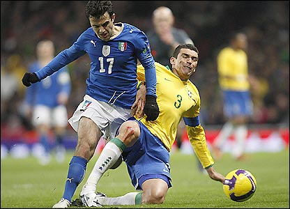 Brazil defender Lucio (left) tackles Italy striker Guiseppe Rossi