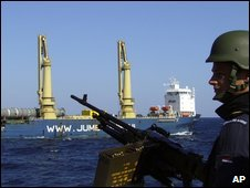 A Dutch navy gunman stands guard as a cargo ship passes near the Gulf of Aden in December 2008