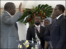 Morgan Tsvangirai (L) takes the oath as premier from President Robert Mugabe (R)