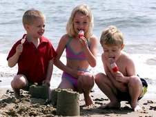 Three children on sandy beach