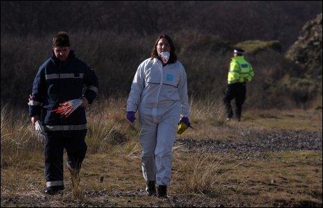 Emergency services personel and air crash scene investigator