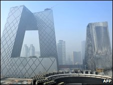 The CCTV building, left, next to the charred remains of the hotel tower on the right, in Beijing