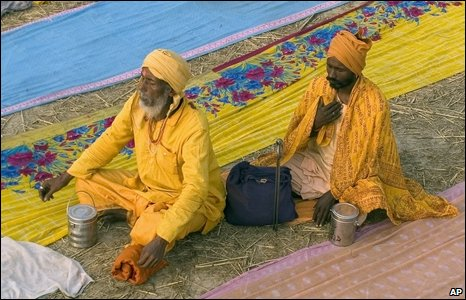 Hindu holy men offer prayers seated between coloured garments left to dry at Sangam, Allahabad, India.