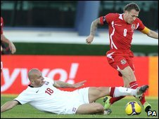 Wales captain Craig Bellamy is tacked by Poland's Mariusz Lewandowski