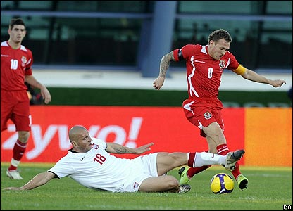 Craig Bellamy is tacked by Poland's Mariusz Lewandowski